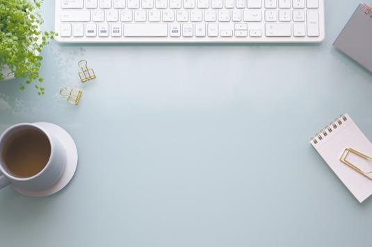 ピンクのノートパソコンの前に広げられたリングノートとボールペン。ミルクティーの入ったカップ&ソーサ。ピンクの腕時計。ピオニーの花。