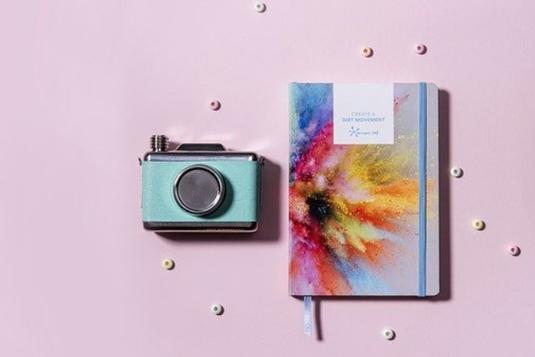 水彩画模様のノートブック。おもちゃのインスタントカメラ。