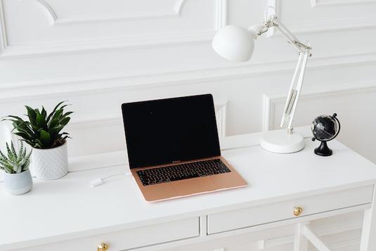 デスクに広げられたノートパソコン、手帳、スマホ、ボールペン、コーヒーの入ったマグカップ。傍らに赤ちゃんのおもちゃ。ガラガラ。