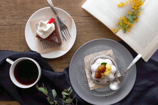 コーヒーが淹れられた白のカップ&ソーサ。白の電卓とボールペン。パソコンのキーボード。無造作に置かれたピンクのチューリップ。