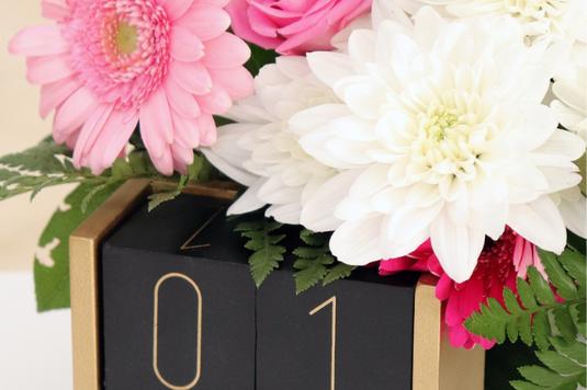 デスクに広げられたカレンダーと万年筆。ダリアの花、デイジーの花。