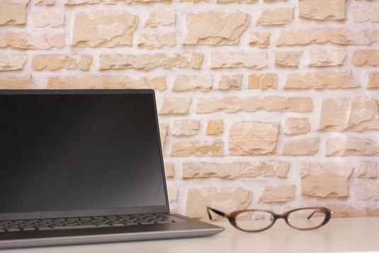 資料、パソコンを広げて会議中のビジネスマン。スーツ姿のエグゼクティブ。