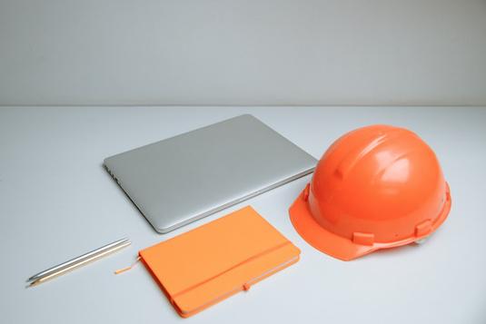会議室でミーティング中の男女。ホワイトボードに書きながら説明する男性。パソコンや資料を広げて聞く女性。