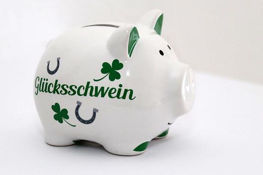 新聞のうえに広げられた革の手帳、リーディンググラス、コーヒーの入った白のマグカップ。観葉植物のつる。