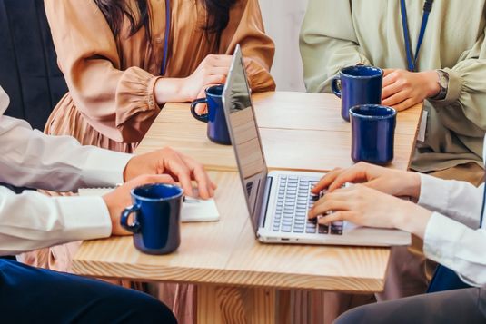オフィスの打ち合わせテーブルでミーティングする男女。めいめいコーヒーを飲みながら。
