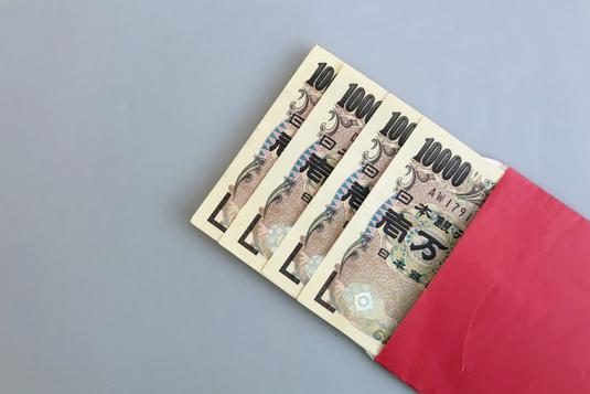 オフィスの打ち合わせテーブルでノートパソコンを広げるビジネスマン。紺のジャケット姿。傍らにマグカップ。