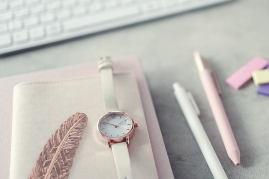 パソコンのキーボード。積み重ねられたノートと手帳のうえに置かれた腕時計と栞。ボールペンと付箋。
