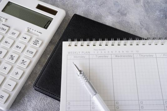 オフィスのオープンスペースでコーヒーを飲みながらミーティングするビジネスパーソン男女4人。
