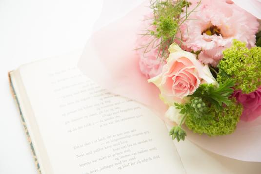 緑がいっぱいの庭に設置されたテーブル。ユリの花が活けられた花びんと赤い背表紙の本が置かれている。