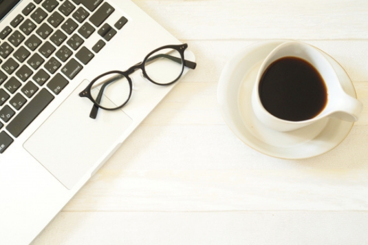 水色と花柄の2冊の手帳のうえに置かれた電卓。メモ帳、マスキングテープ、付箋、ボールペン、ゼムクリップ、コーヒーマグ。