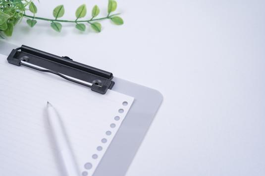 パソコンのキーボード。ピンクの手帳の上に置かれた白の腕時計。ボールペン。カラフルな付箋。