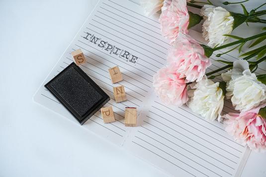 マーブル調のデスクのうえに広げられたノートパソコンとメモ帳、ボールペン。ピンクのガーベラのコサージュ。
