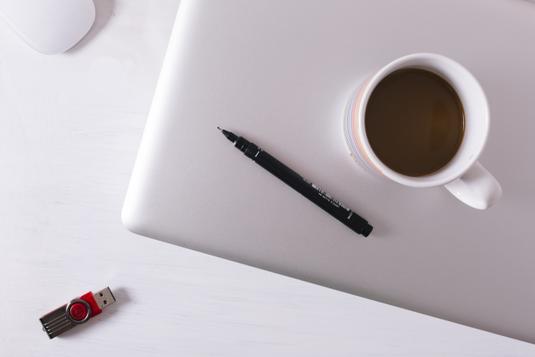 デスクのうえのノートパソコン。マグカップ。ガラスの花びんに活けられた黄色の花。