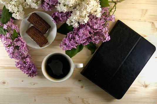 白のサマーセーター、腕時計、カメラ、手帳、コーヒーの入ったマグカップ、眼鏡。