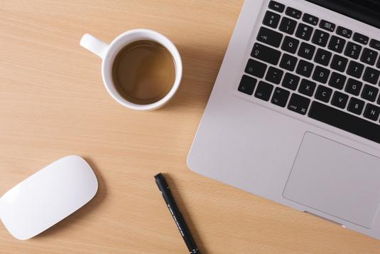 マーブル調のテーブルの上に置かれたイヤフォン。コーヒーの入ったマグカップ。アーモンドクッキーが載った小皿。