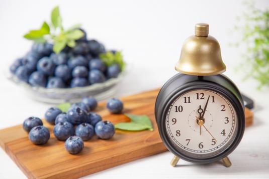 コーヒーの入ったマグカップ。手帳とリングノート。メモ帳。白のバラの花。