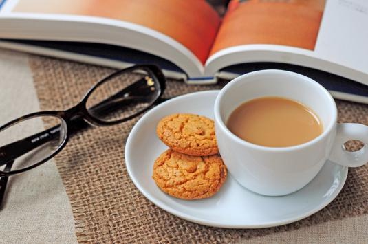 ノートパソコンの前に置かれたピンクのファイル、手帳、電卓。メモ帳とボールペン、ダブルクリップ、コーヒーの入ったマグカップ。