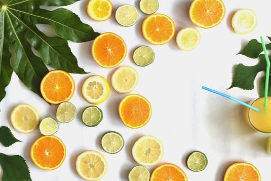 テーブル一面のオレンジとライムの輪切り。傍らにオレンジジュースの入ったグラス。ストロー。