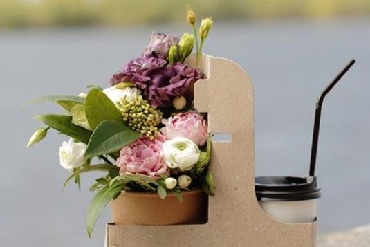 テイクアウトコーヒーと鉢植えの春の花々が入った紙製のBOX。