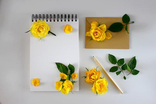 アーモンドクッキーが添えられたホットコーヒー。電卓とパソコンのキーボード。ピンクのチューリップ。