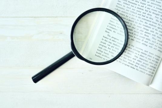 事務所のテーブルで資料をみながら打ち合わせする作業着姿の男女。テーブルの上にヘルメット。観葉植物の鉢植え。