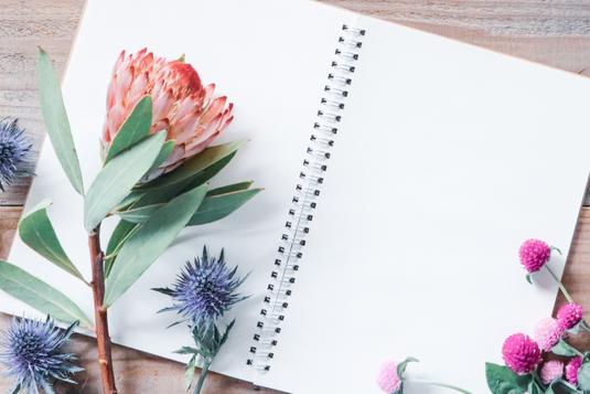 ノートパソコンのまえに置かれたピンクのファイルケース、手帳、電卓。ダブルクリップ。