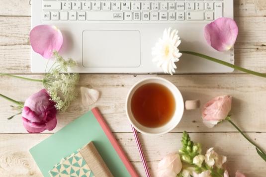 ノートパソコンの前に置かれた紅茶の入ったマグカップ。ノートと手帳、ペン。デイジーとバラ。