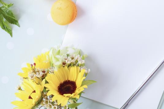ノートの上に置かれたボールペン。オレンジ色のマカロンとひまわりのブーケ。