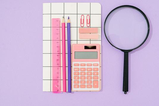 ボールペンを握りしめメモをとるビジネススーツの女性。新入社員。