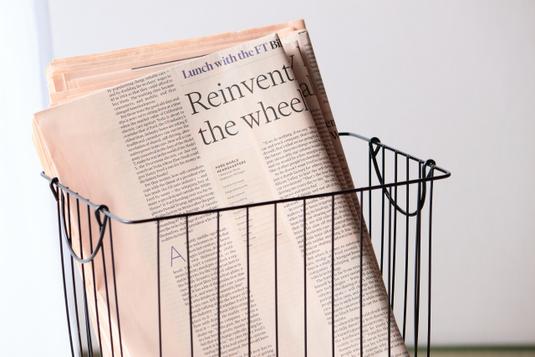 オフィスの打ち合わせテーブルでディスカッションする男女4人。ノートパソコンで議事録をとる女性。