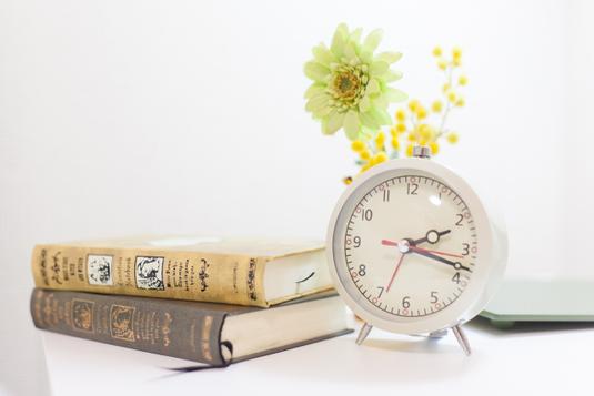 ノートパソコンの横に置かれた飲みかけのコーヒーカップ。資料のペーパー、蛍光マーカーペン、ボールペン。