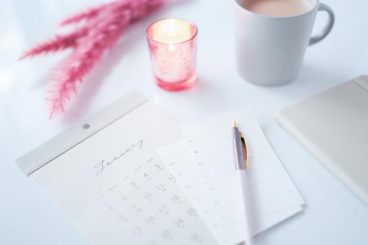 手帳とメモ帳。水色のボールペンと付箋。マスキングテープ。コーヒーの入ったマグカップ。