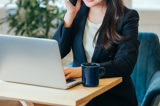 ノートパソコンを広げながら商談するビジネスピープル。スーツ姿の女性と男性。