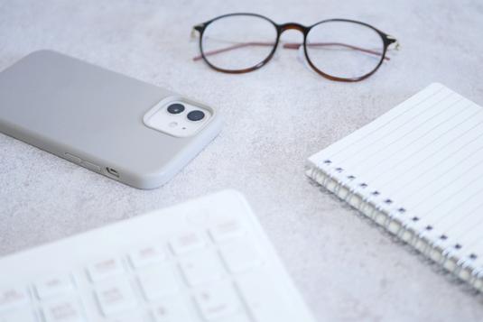 眼鏡、スマホ、パソコンのキーボード、リングノート。