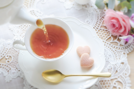 オレンジのガーベラや小手毬の花が活けられた休日のテーブル。紅茶の入ったカップ&ソーサ。ケーキの載った皿。