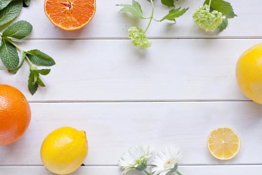 グラスに注がれたオレンジジュユース。葉のついたオレンジの実とくし切りにされたオレンジ。