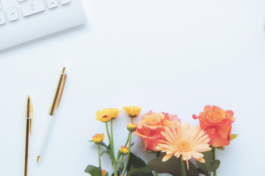 パソコンのキーボード。2本のボールペン。ガーベラ、バラ、メランポジウムの花。