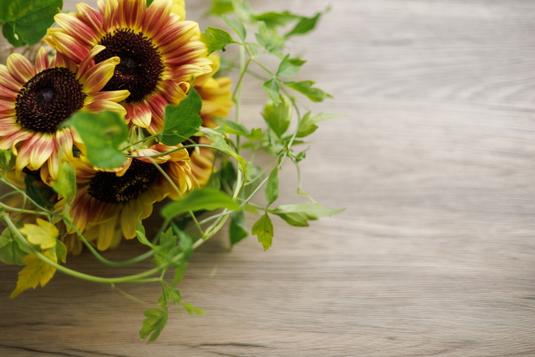 ノートパソコンの前に置かれたメモ帳とピンクのボールペン。カフェオレの入ったピンクのマグカップ。