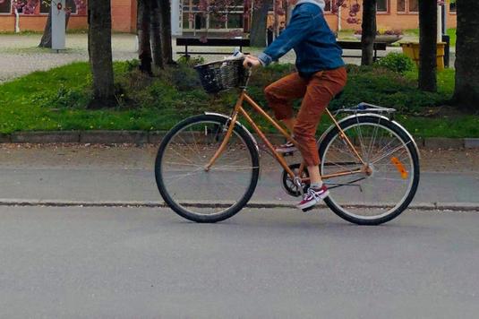 トートバッグを肩にかけ、ノートパソコンを小脇に抱える女性。緑の街を歩く。