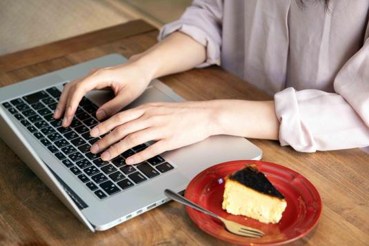 ノートパソコン。ベージュのスケジュール帳と赤の手帳、ボールペン。赤のマグカップに淹れられたカフェラテ。