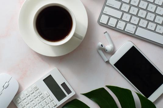 コーヒーの入ったカップ&ソーサ。キーボード、マウス、スマホ、イヤホン、電卓。モンステラの葉。