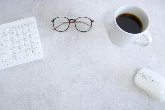 パソコンのキーボードとマウス。眼鏡。コーヒーの入った白のマグカップ。