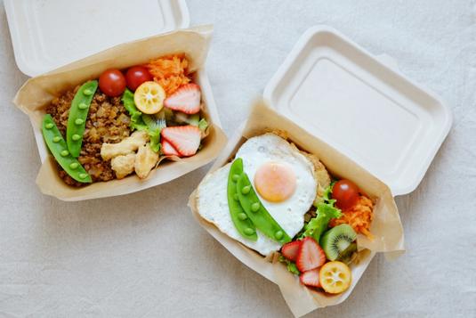 オフィスのフリースペースのテーブルでコーヒーを飲みながら談笑する女性3人。