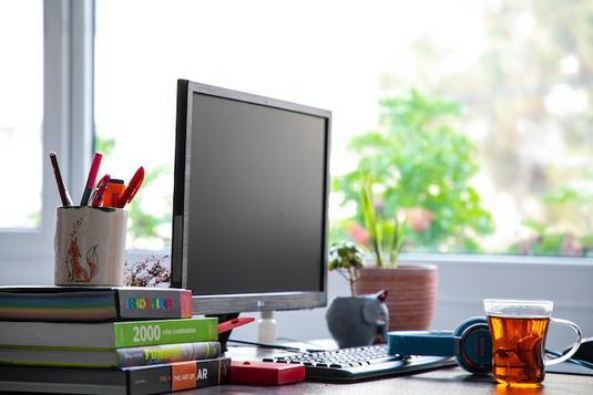 オフィスにおける日常のヒトコマ。ノートパソコンでデータ収集中。ノートパソコンで調べもの。青空のもとそびえたつビルと緑の木々。