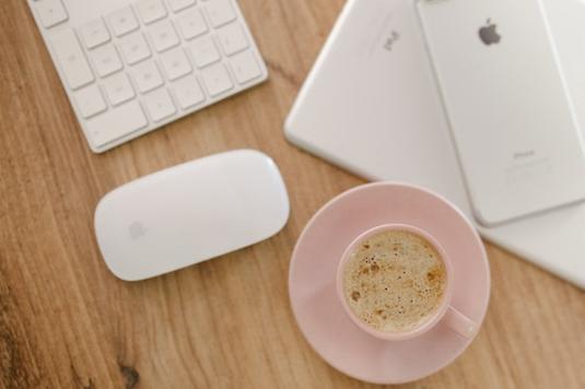 パソコンを前にコーヒーを飲みながらスマホ画面を眺めるビジネスパーソン。リクルートスーツ。新入社員。