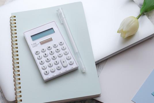 積み重ねられた水色のスケジュール帳、花柄の手帳、ブルーのメモ帳。水色のボールペン。スマートフォン。