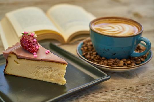 ピンクのノートパソコン。ラナンキュラスのブーケ。紅茶の入った花型のカップ&ソーサ。ピンクのイヤフォン。