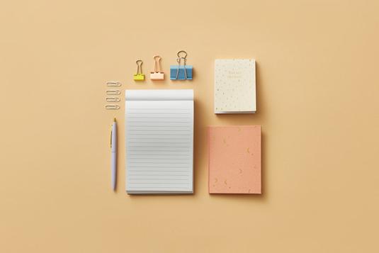 デスクに広げられたノートとボールペン。スマホとイヤホン。傍らに無造作に置かれたピンクのチューリップと白のバラ。
