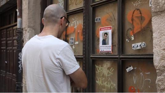 Un hombre observa el cartel en la calle Rúa de los Francos. Ana Burrieza