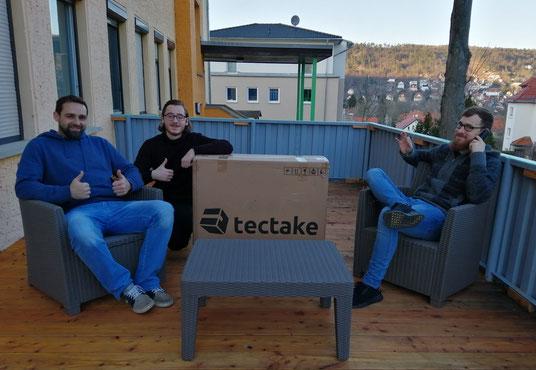 """Zwei Betreuer und ein Jugendlicher aus dem Kinder- und Jugendheim """"Am Friedensberg"""" mit den neuen, noch verpackten Terrassenmöbeln"""